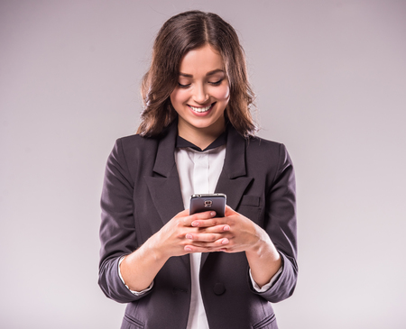 Young woman is writing a message with smartphone, standing on grey background.