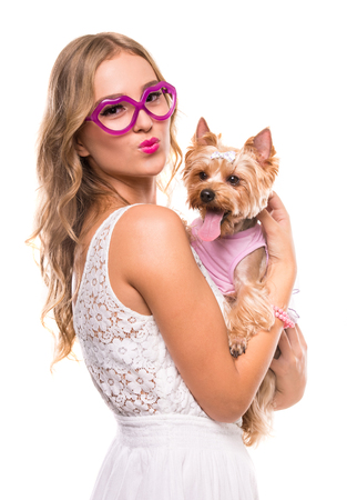 Beautiful young girl in funny glasses and cute yorkshire terrier dog, isolated on white. Stock Photo