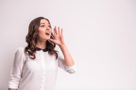 Junge Frau, die ein Geheimnis, stehend auf grauem Hintergrund. Standard-Bild - 48109686
