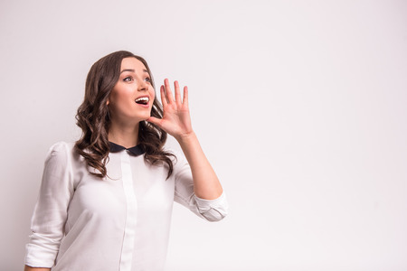 yell: Young woman is telling a secret, standing on grey background. Stock Photo