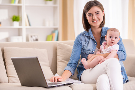 Young woman is working from home, holding baby girl on lap. Stock Photo