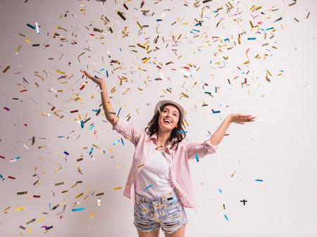 personas festejando: Alegre joven está estirando sus manos mientras confeti cayendo sobre ella. Foto de archivo