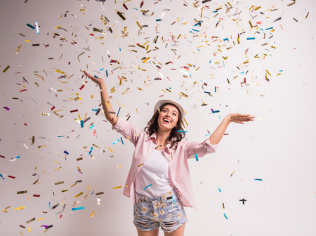 carnival: Cheerful young woman is stretching out her hands while confetti falling on her. Stock Photo