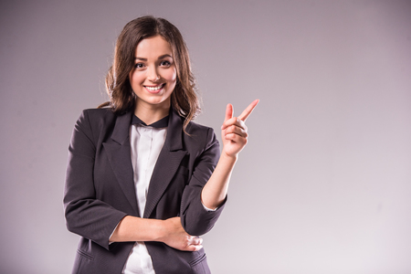 Smiling young woman is pointing at copy space over grey background. Stock Photo
