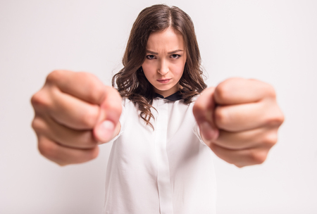 fist fight: Young and angry woman is clenching her fists in rage. Stock Photo