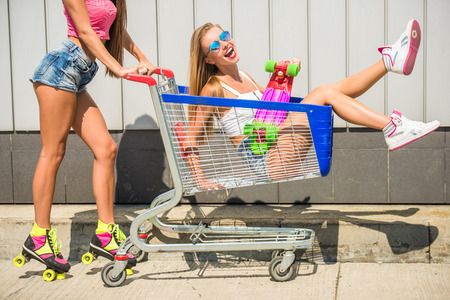 woman shopping cart: Young woman on roller skates is carrying her female friend in shopping cart. Outdoor.