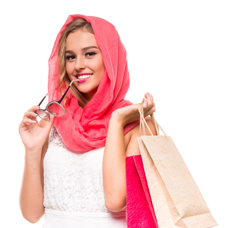 Portrait of a young woman in bright crimson headscarf is holding sunglasses and shopping bags. Beauty, fashion. Stock Photo