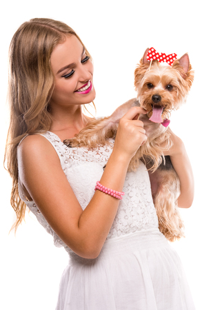 cute blonde: Beautiful young girl with cute yorkshire terrier dog, isolated on white.