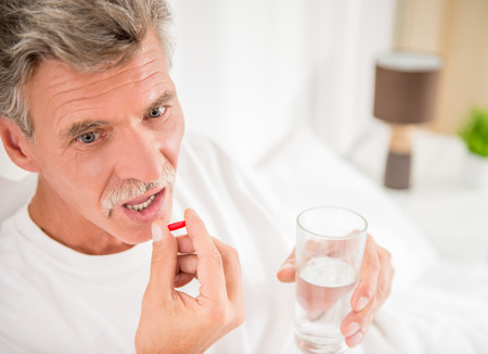infirm: Top view of senior man is drinking water with pills, sitting in bed. Stock Photo