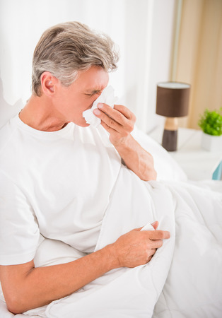 infirm: Senior man is blowing his nose, he has cold. Stock Photo