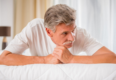 lonliness: Senior man is lying in bed and looking away. Stock Photo
