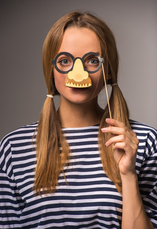 fake smile: Beautiful young woman with two tails is holding fake glasses and nose on her face.