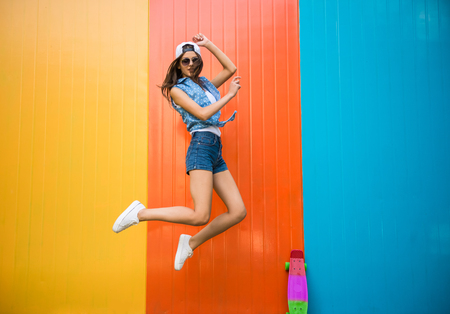 Mooie jonge vrouw is springen met tegen de kleurrijke muur. Stockfoto