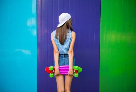 Rear view of young girl in cap standing against the colorful wall and holding skateboard. Stock Photo