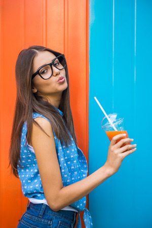 color model: Side view of beautiful girl in glasses is drinking a juice against colorful wall. Stock Photo
