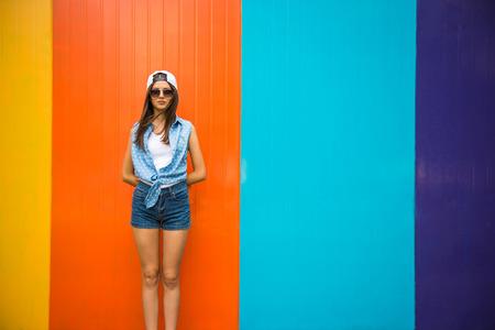Muchacha bonita fresca en gafas de sol y gorra de pie contra la pared colorida.