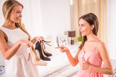 Young woman helps to her female friend choosing a shoes on the date.