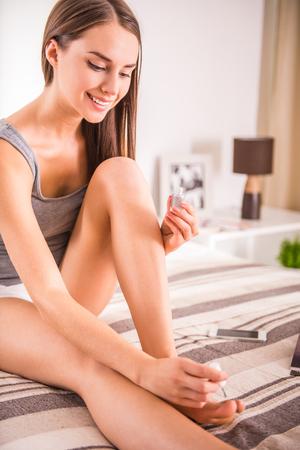 pedicura: Mujer joven atractiva que barniza sus uñas de los pies sobre la cama en su casa.