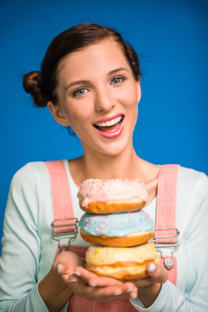 pastries: Smiling woman is holding donuts standing against blue background.