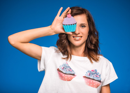 endorphines: Young woman with muffin on blue background.