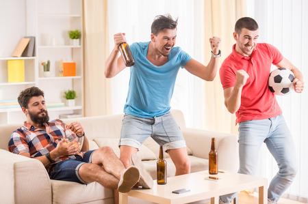 젊은 남자가 맥주를 마실 피자를 먹고 축구 응원