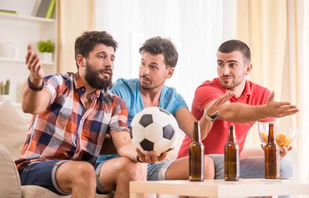 hombre tomando cerveza: Los hombres j�venes beben cerveza, comer pizza y v�tores para el f�tbol