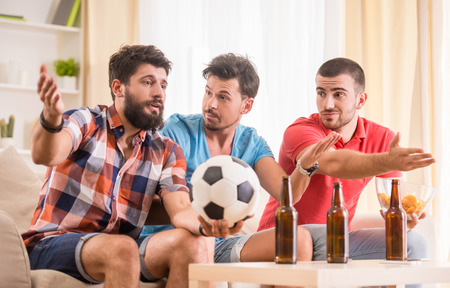 young man: Young men drink beer, eat pizza and cheering for football
