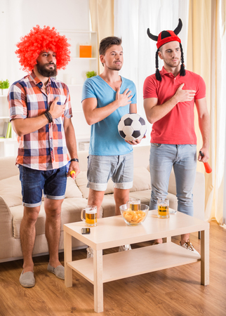 indoor soccer: Young men drink beer, eat pizza and cheering for football