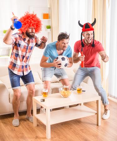 Junge Männer trinken Bier, essen Pizza und jubeln für Fußball Standard-Bild - 45655829