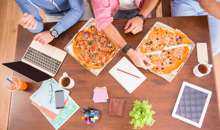 business partnership: Businessmen in casual style use computers in office and eat pizza Stock Photo