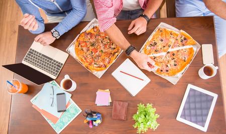 negocios comida: Empresarios en los ordenadores de uso ocasional estilo en oficina y comer pizza