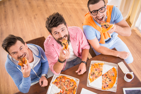people eating: Businessmen in casual style use computers in office and eat pizza Stock Photo