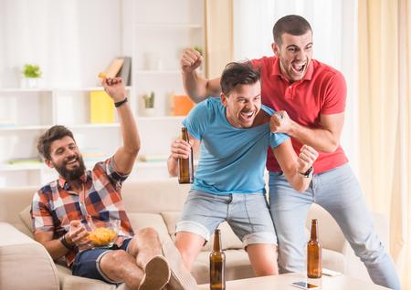 Los hombres jóvenes beben cerveza, comer pizza y vítores para el fútbol
