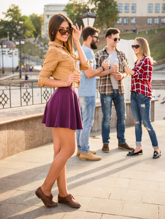 drinks on bar: Young happy people walking outdoors. Drinking beverages Stock Photo