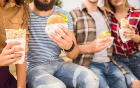 mat: Ungdomar promenader utomhus. Sitter i parken och äter snabbmat Stockfoto