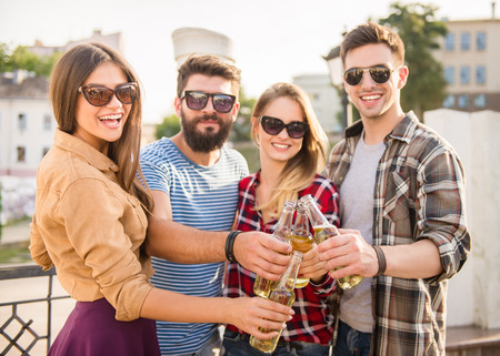 Young happy people walking outdoors. Drinking beverages Standard-Bild