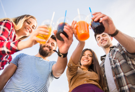 outdoors: Young happy people walking outdoors. Drinking beverages Stock Photo