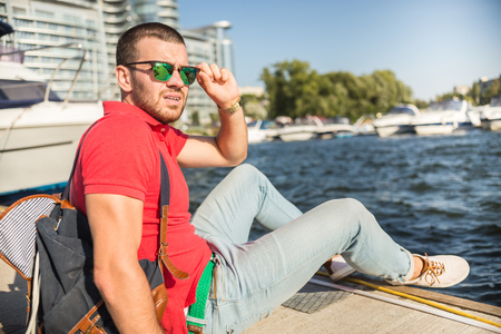laugher: Young successful businessman holding time on the yacht.