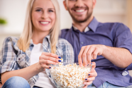 bowl of popcorn: Loving young couple at home sitting on the couch, watch TV and eat popcorn