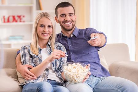 ver television: Amantes de la pareja joven en su casa sentado en el sof�, ver la televisi�n y comer palomitas de ma�z Foto de archivo