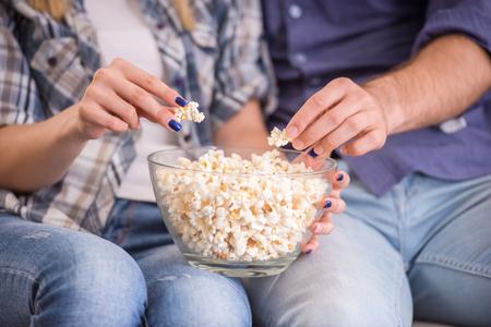 palomitas de maiz: Amantes de la pareja joven en su casa sentado en el sofá, ver la televisión y comer palomitas de maíz Foto de archivo