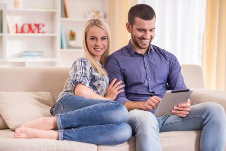 Liefdevolle jong stel zit op de bank thuis, met behulp van een tablet Stockfoto