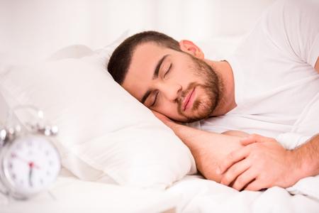 Homem novo que dorme na cama confortável em casa.