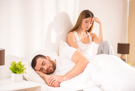 pareja en la cama: Problemas familiares. Joven pareja tiene problemas Foto de archivo
