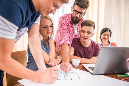 personas pensando: Un grupo de gente joven que trabaja en la oficina