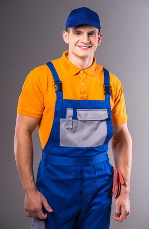 Portrait of a young man in work clothes on a gray background 版權商用圖片
