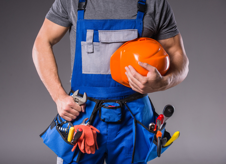 Construction work. Portrait of a young builder with tools in hand to build on gray background