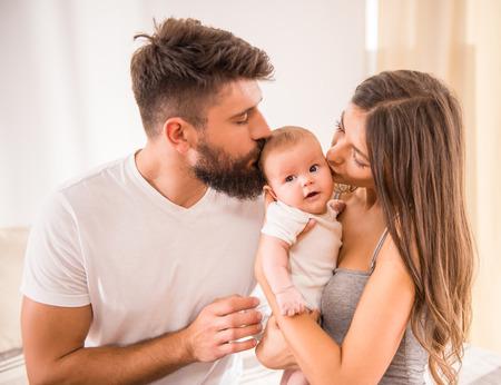 papa: Portrait de jeunes heureux parents avec un b�b� dans le lit � la maison