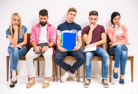 line of people: Group of people sitting on chairs waiting interviews Stock Photo