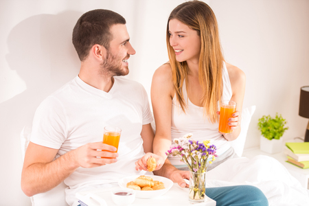 romance bed: Breakfast in bed. Young happy couple eating breakfast in her bedroom Stock Photo